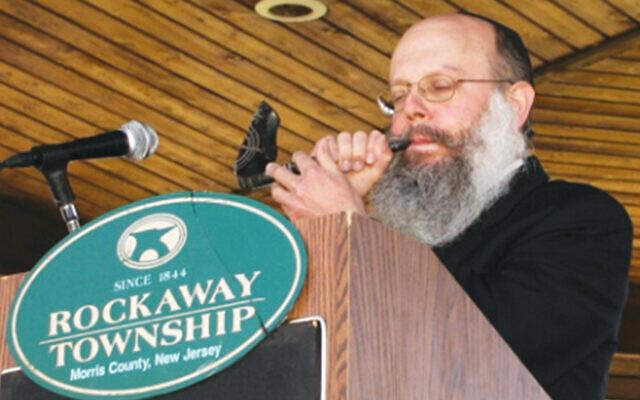 Rabbi Asher Herson blows the shofar at a pre-Rosh Hashanah municipal gathering in Rockaway Township.