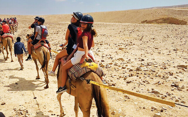 Yaara Nahar, right, looks back from her seat on a camel.