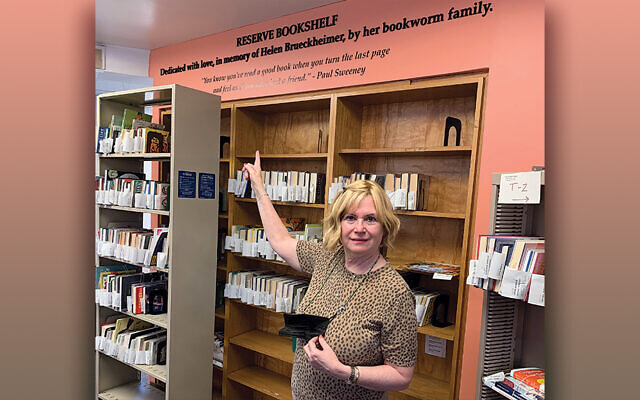 Ms. Kook stands at the Teaneck library's reserve section, near the sign in memory of Helen Brueckheimer.