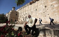 A Jewish settler sits outside the Tomb of the Patriarchs in the West Bank city of Hebron (photo credit: Kobi Gideon/Flash90)