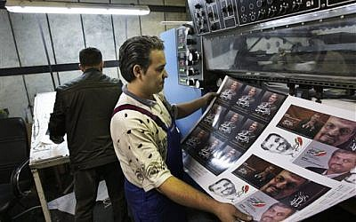 Printed posters of Mostafa Kavakebian, a candidate in the upcoming election, in a printing house in Tehran (photo credit: AP/Vahid Salemi)
