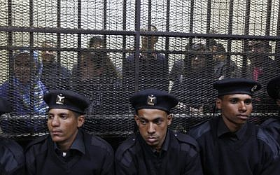 Egyptian policemen sit in front of Egyptian employees of several pro-democracy groups charged with using foreign funds to foment unrest during their trial in Cairo, Egypt. (photo credit: AP/Khalil Hamra)