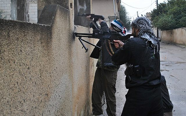 Syrian rebels take their position behind a wall as they fire their guns during a battle with the Syrian government forces, at Rastan area in Homs province, central Syria, on Tuesday Jan. 31, 2012. (photo credit: AP)