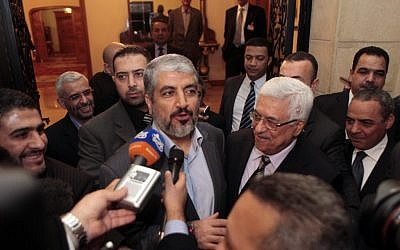 Mahmoud Abbas (center right) and Hamas leader Khaled Mashaal speak to reporters after talks in Cairo in February 2012 (photo credit: Amr Nabil/AP)