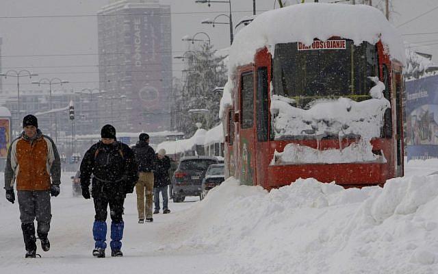 Bosnians walk near a frozen tram in the Bosnian capital of Sarajevo, on Saturday, Feb. 4, 2012. (photo credit: AP/Amel Emric)
