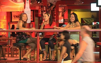Female prostitutes sit by a bar in Phuket, Thailand (photo credit: Nati Shohat/Flash90)