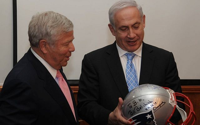 Robert K. Kraft (left) hands Israeli Prime Minister Benjamin Netanyahu a helmet signed by the New England Patriots football players in February 2012. (Photo credit: Amos BenGershom / GPO/Flash90)