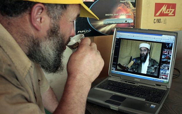 A man in Hebron watches the news on his computer. (photo credit: Najeh Hashlamoun /Flash 90)
