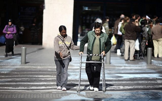 Illustrative: A carer helping an elderly Israeli to cross the street in Tel Aviv. (Kobi Gideon/Flash90)