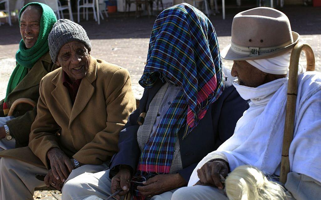 Ethiopian Jews sitting in the sun in Ashkelon in late January. (Photo credit: Tsafrir Abayov/Flash90)