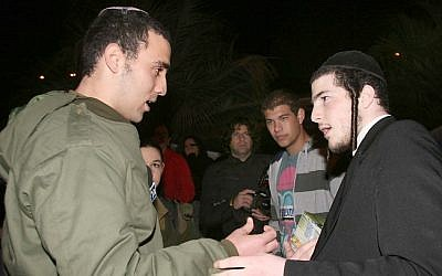 An Orthodox soldier and an ultra-Orthodox Israeli. (photo credit: Gideon Markowicz/Flash90)