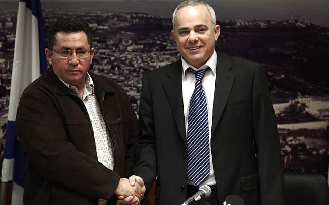 A stern looking Histadrut Chairman Ofer Eini shakes hands with smiling Finance Minister Yuval Steinitz during a joint press conference Sunday morning after all-night negotiations that ended the general strike (photo credit: Uri Lenz/Flash90)
