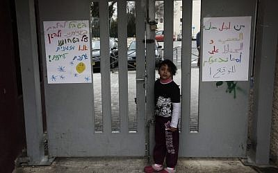 An Arab girl stands near signs against racism at the entrance of the Max Rayne Hand in Hand school for Bilingual education in Jerusalem (photo credit: Kobi Gideon/Flash90)