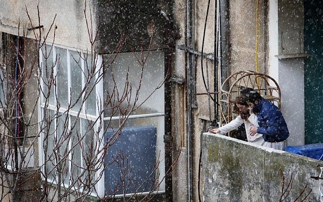 Young Israelis look at the snow falling down in Jerusalem. (photo credit: Miriam Alster/Flash 90)