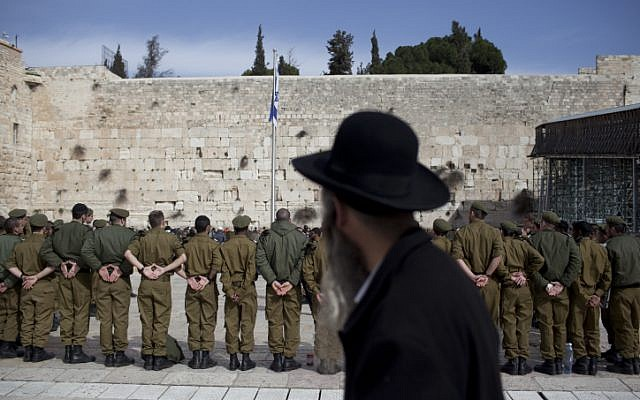 An ultra-Orthodox man observes a group of soldiers at the Western Wall in Jerusalem (illustrative photo: Yonatan Sindel/Flash90)