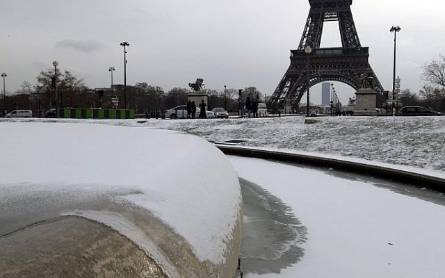 People look at the snow at the Trocadero near the Eiffel Tower seen in background, in Paris, Sunday Feb. 5, 2012.  (photo credit: AP/Jacques Brinon)