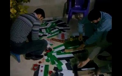 Volunteers paint opposition flags in Idlib, Syria (photo credit: Ugarit News)
