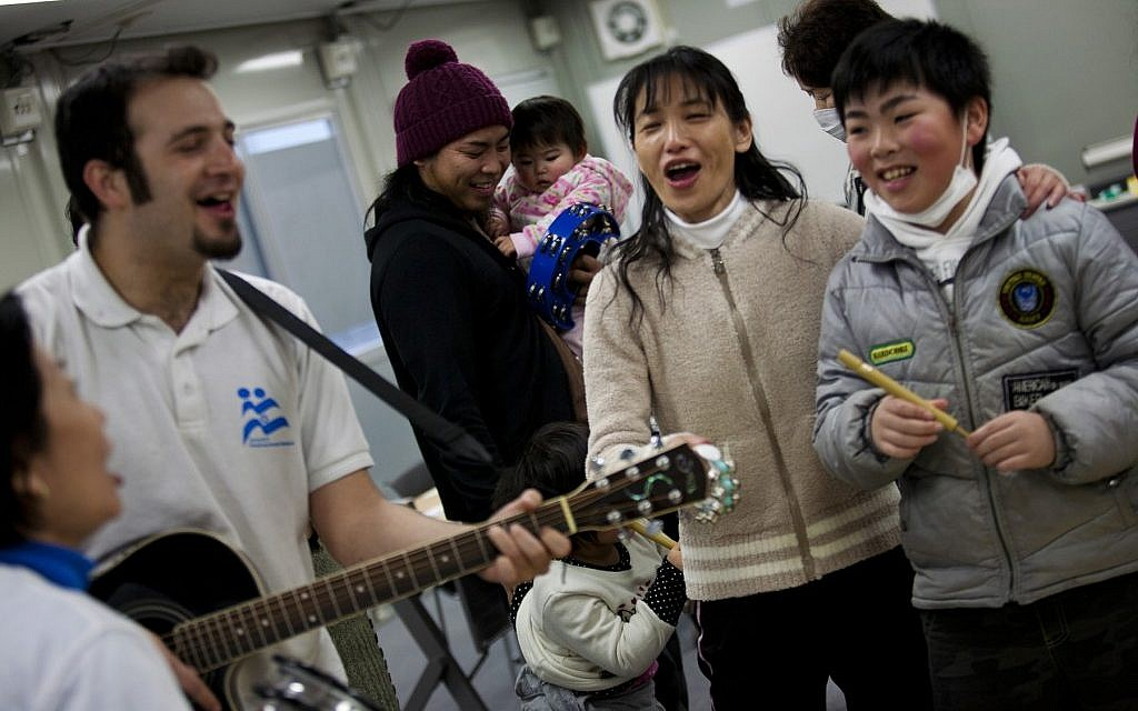 Yotam Polizer, IsraAID's Japan project manager, plays guitar for residents of a temporary housing site for tsunami survivors in Ishinomaki as part of a music therapy session (photo credit: Boaz Arad/JTA)