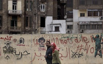A couple walks by a grafittied wall in Cairo. (photo credit: AP/Muhammed Muheisen)