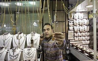 An Iranian goldsmith adjusts a gold necklace at the gold market of Tehran's old main bazaar. (photo credit: c/o AP)