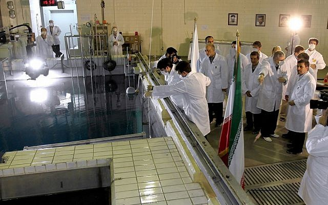 Iranian President Mahmoud Ahmadinejad, right, is escorted by technicians during a tour of Tehran's research reactor center in February 2012 (photo credit: AP/Iranian President's Office)