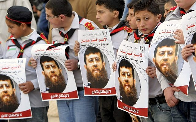 Palestinian schoolboys hold images of Khader Adnan, in the West Bank city of Jenin last week. (photo credit: AP/Mohammed Ballas)