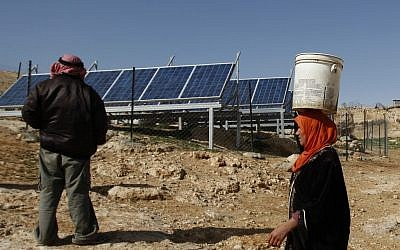A Palestinian woman carries a bucket of water next to solar panels in Al-Thala. (photo credit: AP/Majdi Mohammed)
