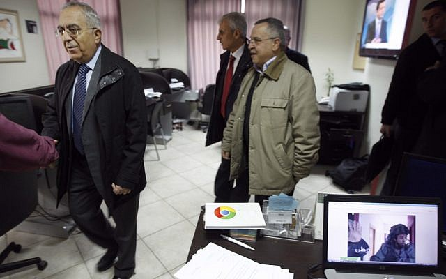 Palestinian Prime Minister Salam Fayyad (left) visits the offices of al-Watan TV after a pre-dawn IDF raid in Ramallah on Wednesday. The computer screen on the right shows a soldier during the raid. (photo credit: AP/Majdi Mohammed)