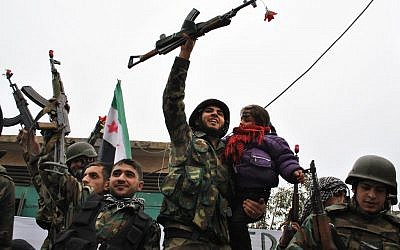 Syrian army defectors celebrate shortly after they joined the anti-Syrian regime protesters at Khaldiyeh area in Homs province, central Syria, in January 2012. (Photo credit: AP/File photo)