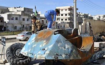 Syrian girls play on top of a destroyed Syrian riot police tank in the Bayada neighborhood in Homs province, Syria. The EU expanded its financial sanctions against the Assad regime on Monday 27th February 2012 to try and bring an end to the violence. (photo credit: AP)