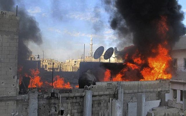 A house burns after Syrian government shelling in the Baba Amr neighborhood in Homs province, in this citizen journalism image. (file photo; photo credit: AP/Local Coordination Committees in Syria)