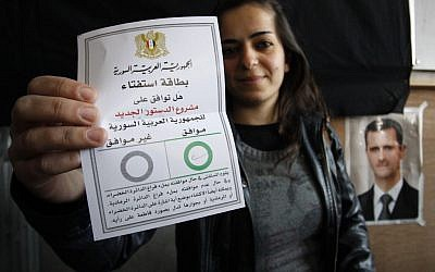 A Syrian woman shows her ballot paper at a polling station during a referendum on the new constitution in Damascus on Sunday (photo credit: AP/Muzaffar Salman)