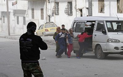 Civilians flee after Syrian Army tanks entered the northwestern city of Idlib on Tuesday. (photo credit: AP)