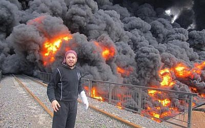 An anti-Syrian regime activist stands in front of flames and black smoke from a bombed oil pipeline in Homs, Syria in February 2012 (photo credit: AP Photo/Local Coordination Committees in Syria)