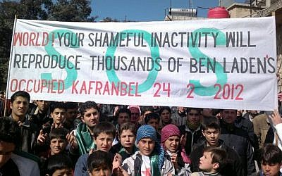 In this Feb. 24, 2012 imageanti-Syrian regime protesters hold a banner during a demonstration, in Kafranbel near Idlib, north Syria. (photo credit:AP/Local Coordination Committees in Syria)