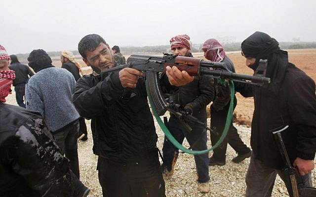 A member of the Free Syrian Army takes aim during weapons training outside Idlib, Syria, (photo credit: AP)