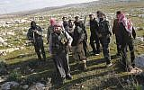 Syrian rebels are seen outside of Idlib, Syria, Saturday. The foreign ministers of the Arab League are meeting in Cairo Sunday to decide on re-sending an observer mission to Syria amid the dramatic surge in violence. (photo credit: AP)