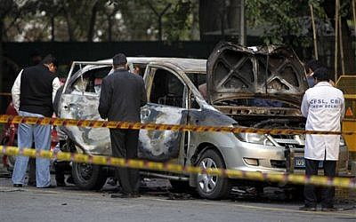 Indian security and forensic officials examine a car belonging to the Israel Embassy after an explosion tore through the vehicle in New Delhi on Monday. (photo credit: AP Photo/Mustafa Quraishi)