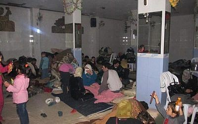 In this undated citizen journalism image accessed on Thursday, Syrian families gather at a shelter hiding from Syrian government forces shelling, in the Baba Amr neighborhood of Homs province. (photo credit: AP Photo/Local Coordination Committees in Syria)