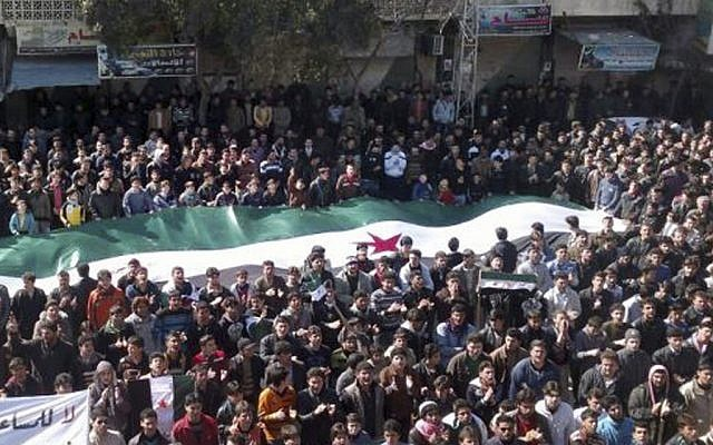 Anti-regime protesters carry a giant Syrian revolution flag in Idlib, Syria, last week. (photo credit:AP/Local Coordination Committees in Syria)
