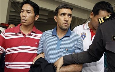 Thai immigration officers escort detained Iranian Mohammad Kharzei, center, at the immigration headquarters in Bangkok on Thursday. Kharzei and two fellow Iranians arrested after accidentally setting off an explosives cache in Bangkok were planning to attack Israeli diplomats, Thailand's police chief said. (AP Photo/Sakchai Lalit)