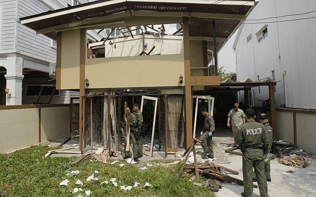 Thai Explosive Ordnance Disposal (EOD) officials examine the damage caused by a blast at the house where suspected bombers were staying in Bangkok, Thailand. (photo credit: AP/Sakchai Lalit)