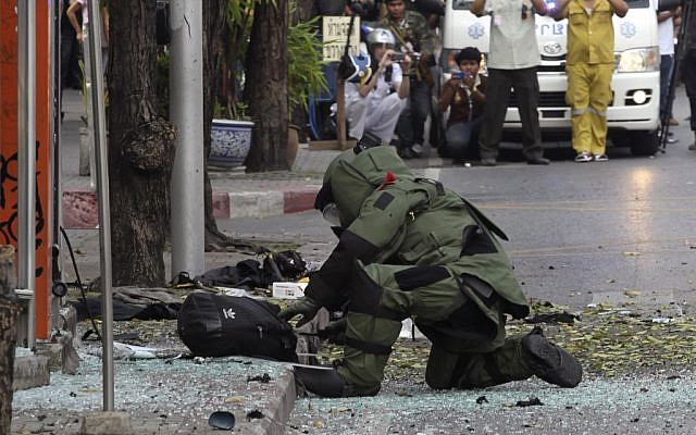A Thai Explosive Ordnance Disposal official examines a backpack left at the bomb site in Bangkok last week (photo credit: AP/Apichart Weerawong)