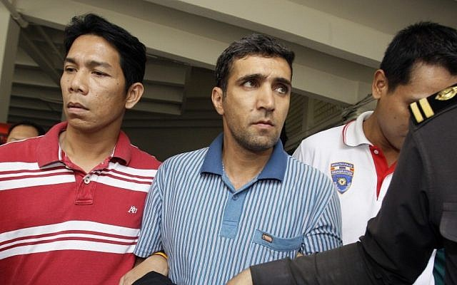 Thai immigration officers escort detained Iranian Mohammad Kharzei, center, at the immigration headquarters in Bangkok. (photo credit: AP)