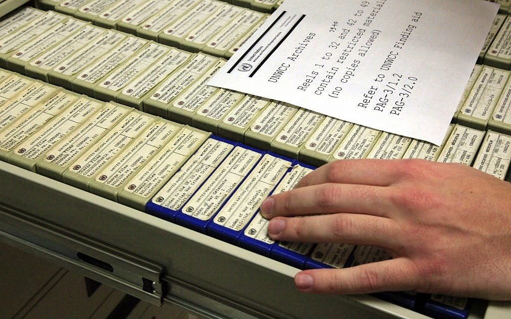 A researcher in New York opens a drawer containing some of the 184 reels of microfilmed documents with data on World War II criminals. (photo credit: AP/Bebeto Matthews)