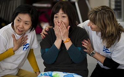 Yuriko Kohata, who saved her father and her son from the tsunami, is comforted by IsraAID project coordinator/translator Celia Dunkelman, left, and therapist Osnat Nisanov, right, at a workshop in one of Iwanuma's many temporary housing sites. (photo credit: Boaz Arad)