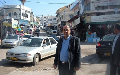 Zidan Badran, mayor of the Israeli portion of the Arab town of Barta'a, stands on the seam that separates the Israeli part of town from its West Bank portion. (photo credit: Linda Gradstein/JTA)
