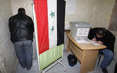 A Syrian man, left, signs ballot papers inside a voting booth at a polling station during a referendum on the new constitution in Damascus, Syria, Sunday Feb. 26, 2012 (photo credit: AP/Muzaffar Salman)