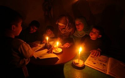 Palestinian children do their homework by candlelight at their home in a refugee camp in Gaza City (photo credit: Abed Rahim Khatib/Flash 90)