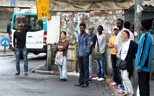 Many migrant workers, like these at a bus stop in South Tel Aviv, and their families could be deported in the coming month. (photo credit: Nicky Kelvin/Flash90).